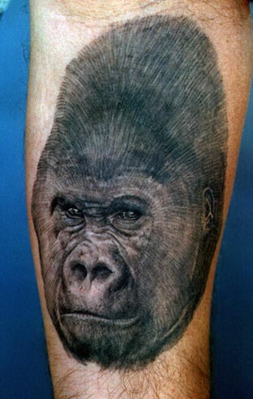 Severe black-ink gorilla head tattoo on arm