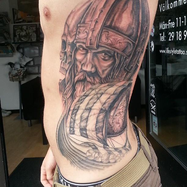 Ship on the background of Viking head tattoo on back