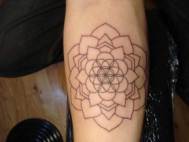 Simple black-contour flower of life tattoo on arm