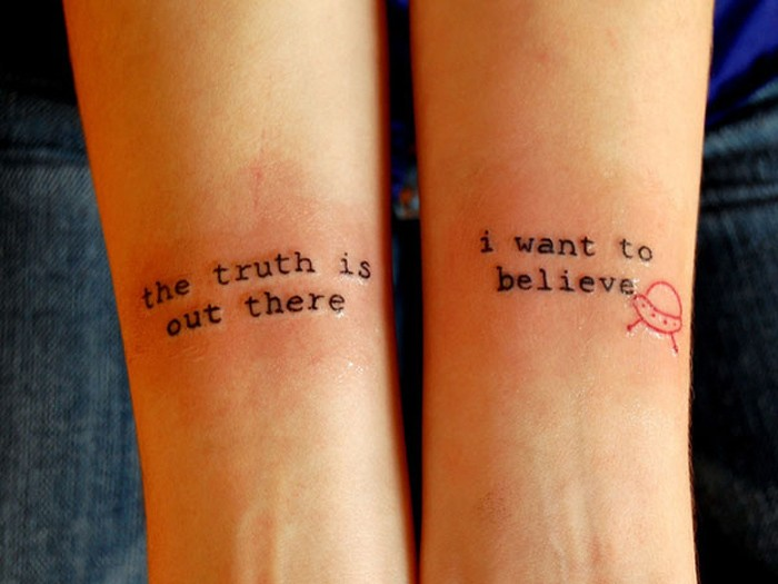 Simple printed quote with tiny red flying saucer tattoo on arm