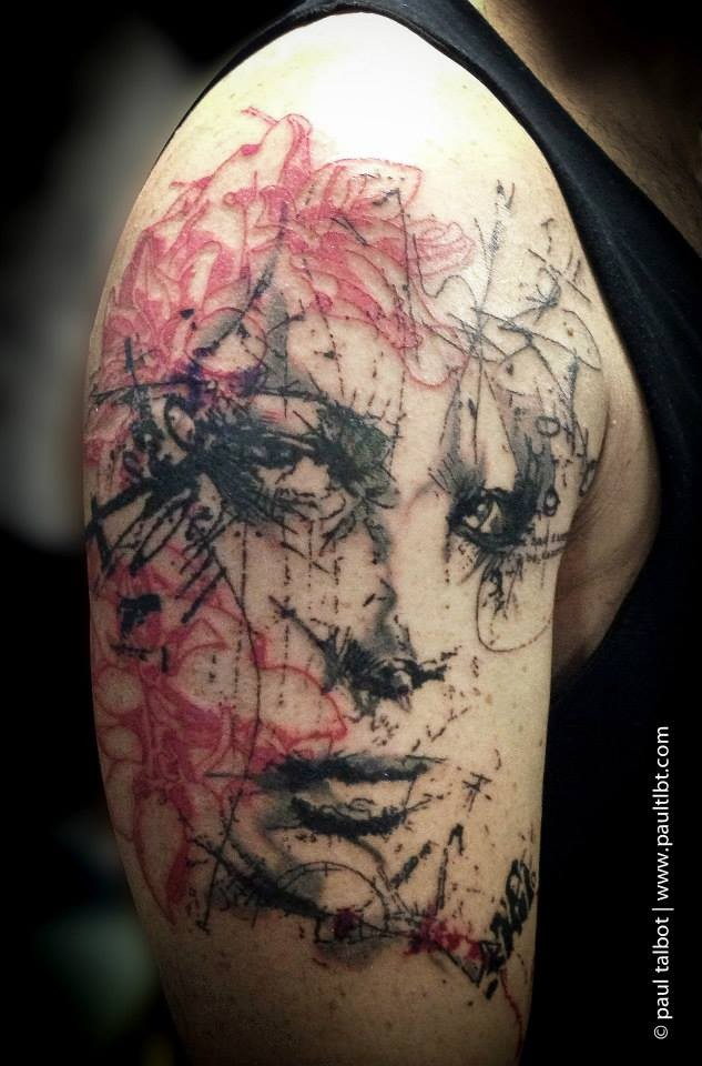 Sketch style colored upper arm tattoo of woman portrait combined iwth various ornaments