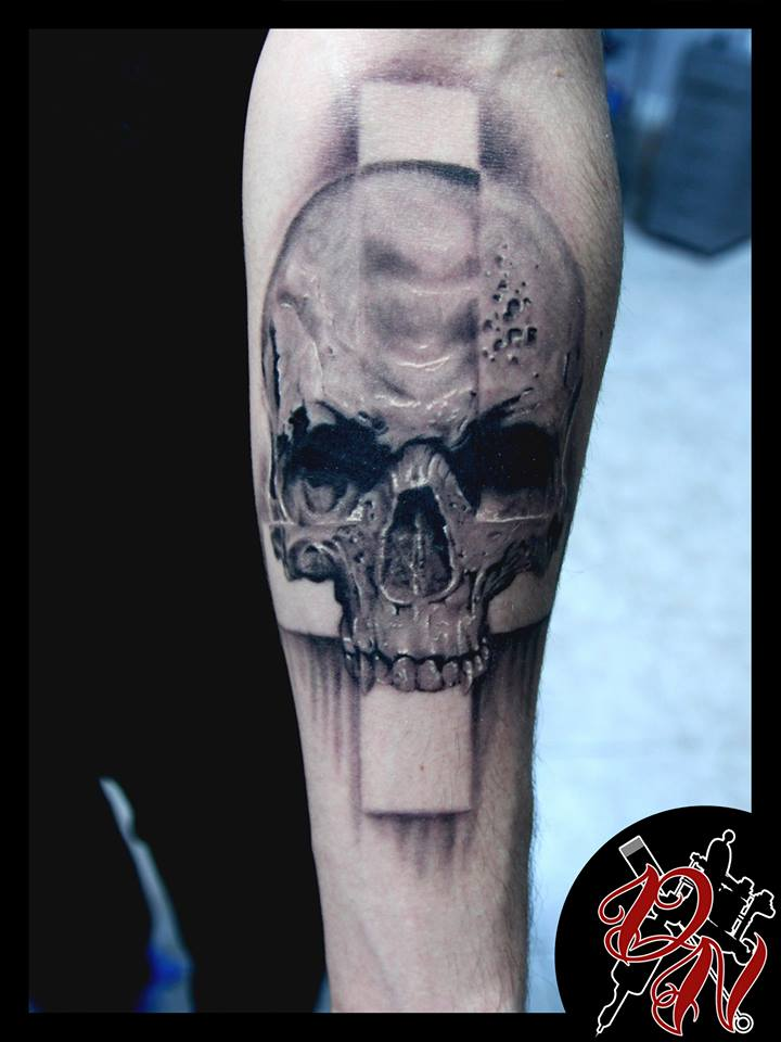 Skull and cross tattoo on forearm