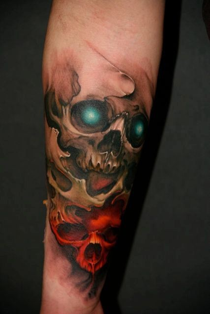 Skull with emerald eyes and red skull tattoo on arm