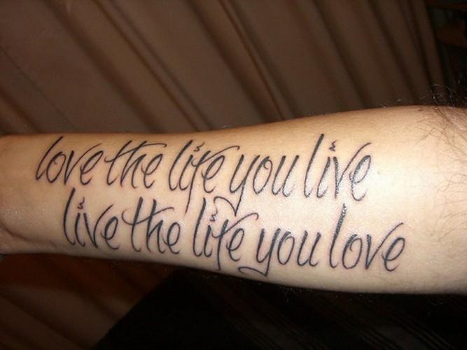 citazione intelligente lettere nere tatuaggio su braccio