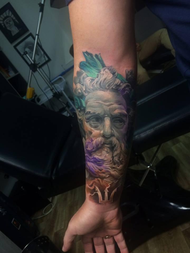 Statue face tattoo on forearm