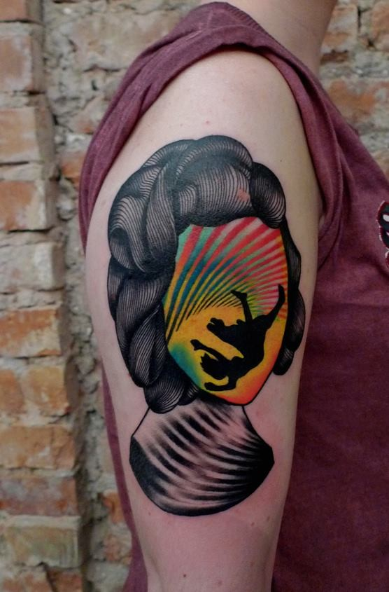 Strange looking colored on upper arm tattoo of woman head stylized with falling man