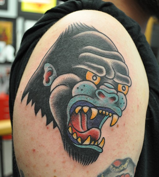 Super old school colorful gorilla head tattoo on upper arm