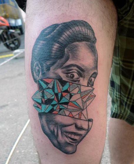 Surrealistic painted by Mariusz Trubisz thigh tattoo of man face with geometrical ornaments