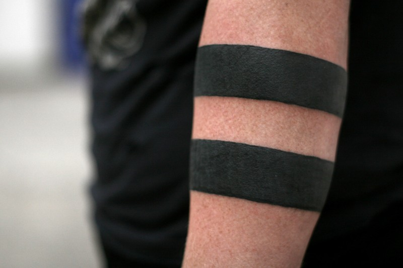Thick-line black band tattoo on forearm