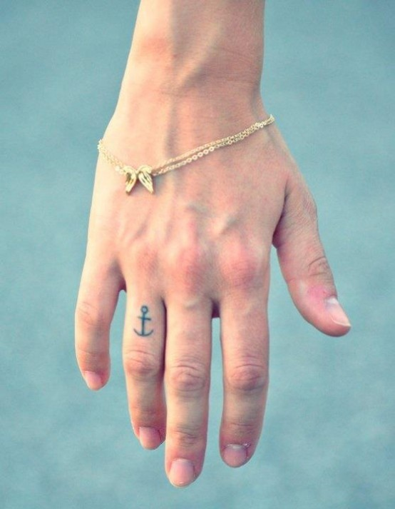 Thin-lined black anchor tattoo on ring finger