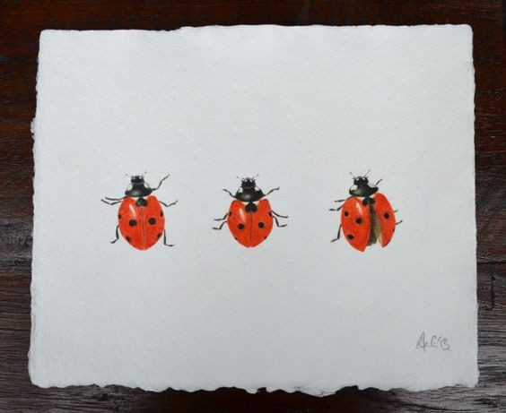 Three small watercolor ladybugs in different poses tattoo design