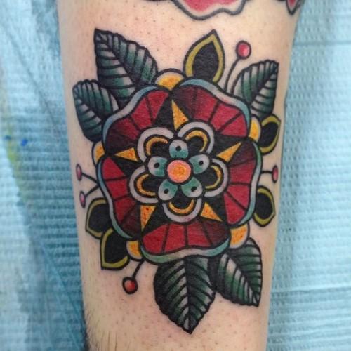 Tatuaje en el brazo, flor roja tradicional con ojas verdes oscuros
