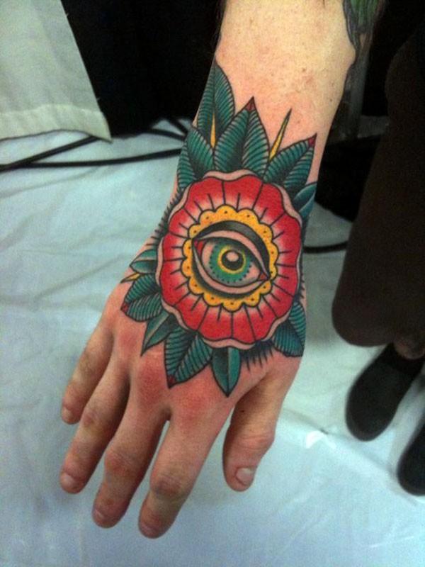 Tatuaje en la mano,  flor extraño con ojo verde