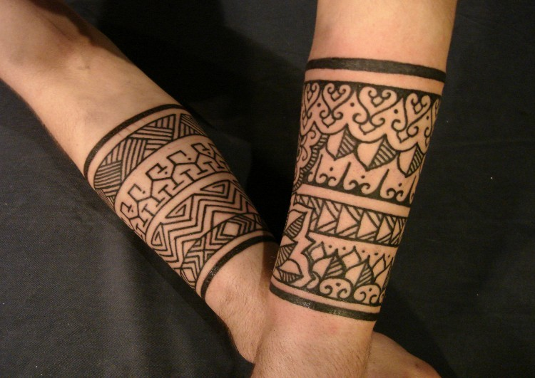 Traditional tribal band tattoos on forearms