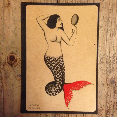 Unusual mermaid with red tail flipper looking in the mirror tattoo design