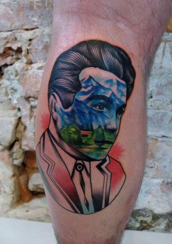 Unusuzl ha disegnato un tatuaggio a gamba colorata di un uomo stilizzato con la montagna di Mariusz Trubisz