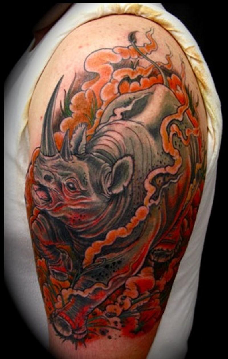 Tatuaje en el brazo, rinoceronte imponente en el humo rojo