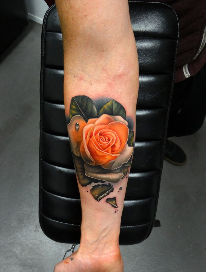 Very realistic rose tattoo on forearm