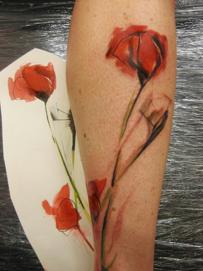 Watercolor poppy flower on stem tattoo on arm