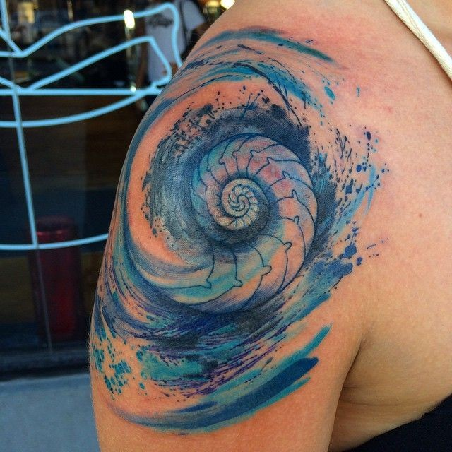 Watercolor style colored shoulder tattoo of nautilus