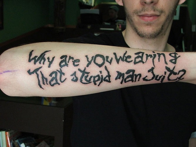 Why are you wearing that stupid man suit quote tattoo on arm
