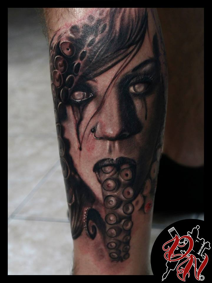 Woman face and tentacles tattoo on forearm