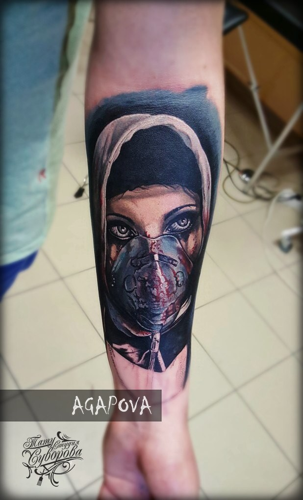 Woman in mask tattoo on forearm