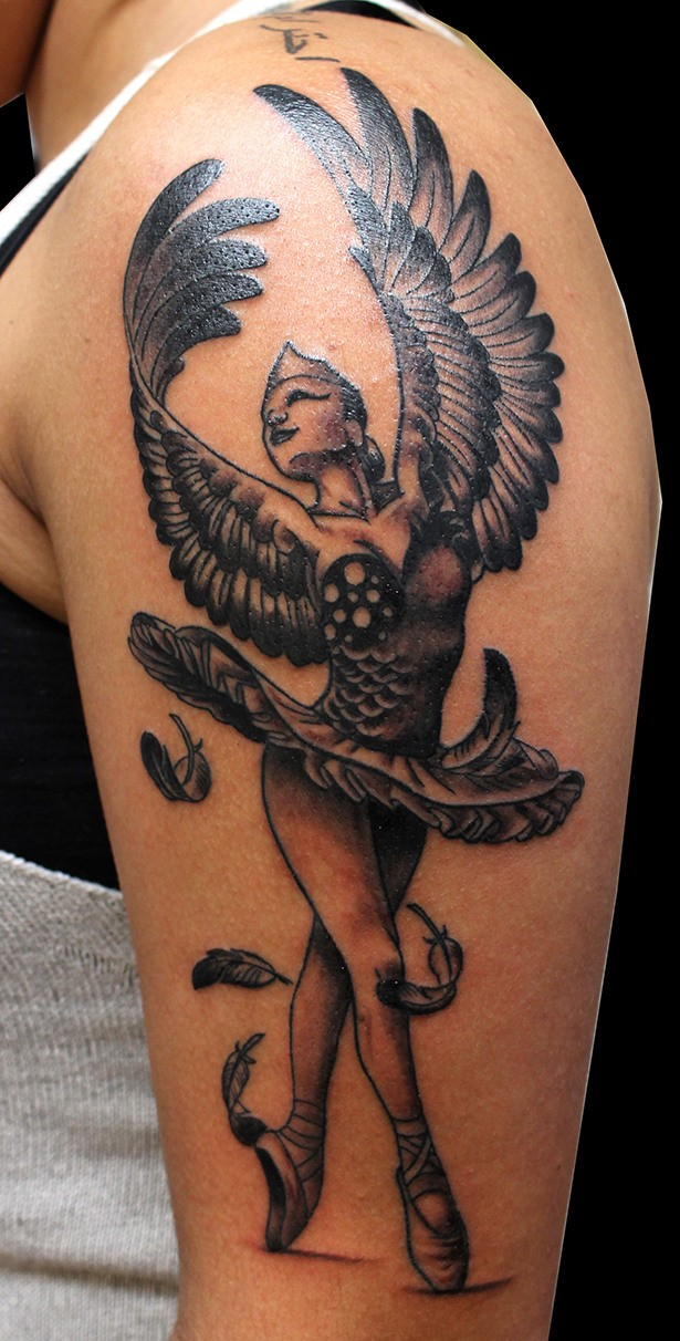 Wonderful black-ink ballerina with swan wings tattoo on upper arm