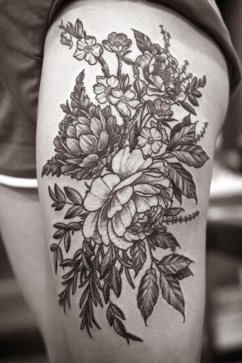 Tatuaje en el muslo,  planta con flores descolorida
