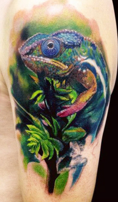 Wonderful colored chameleon sitting on tree branch tattoo on upper arm