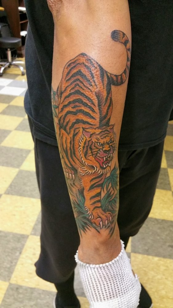 Wonderful colorful hunting tiger tattoo on outer forearm