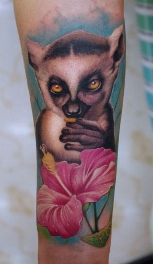 Wonderful realistic colorful lemur with pink flower tattoo on arm