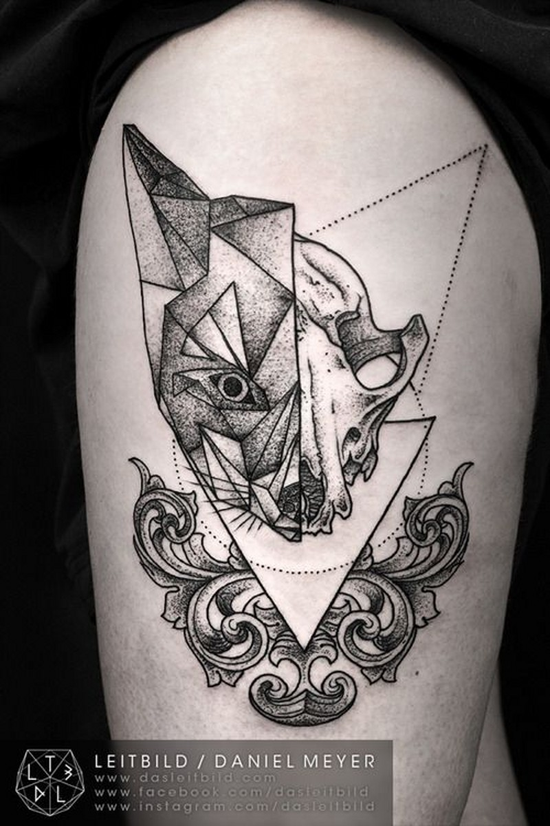 Abstract geometrical style black ink half fox half skull tattoo on thigh