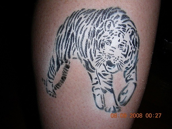Abstract homemade like black and white tiger tattoo on leg muscle