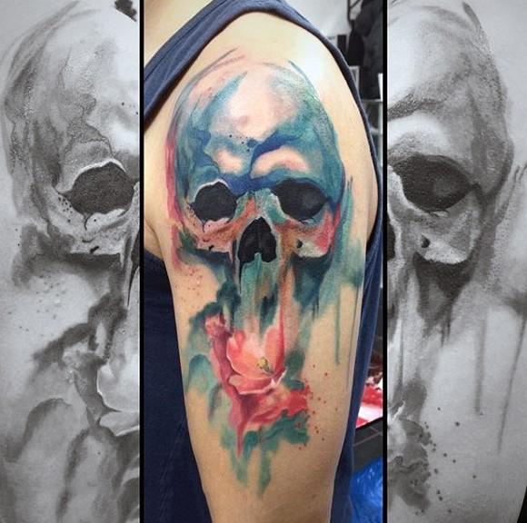 Tatuaje en el brazo, cráneo borroso de acuarelas  con flor bella