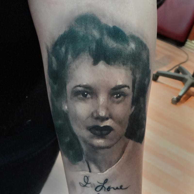 Abstract style black and white woman portrait tattoo on upper arm