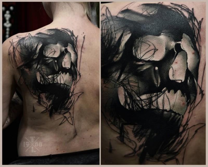 Abstract style black ink back tattoo of demonic like skull