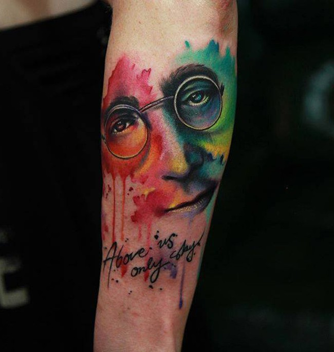 Abstract style colored arm tattoo on Lennon face with lettering