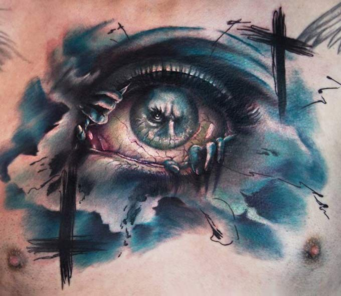 Abstract style colored chest tattoo of creepy looking eye with demon and black cross