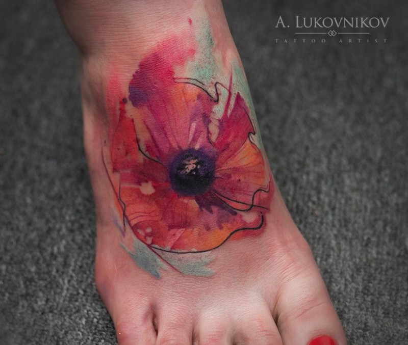 Abstract style colored foot tattoo of small flower