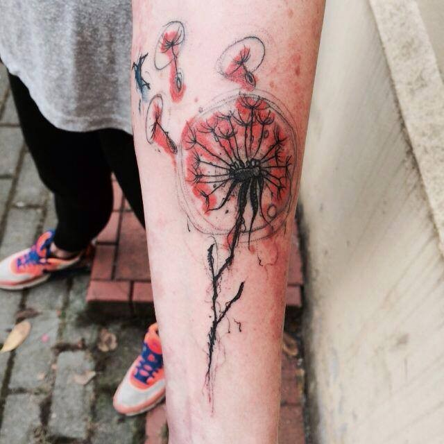 Abstract style colored forearm tattoo of dandelions