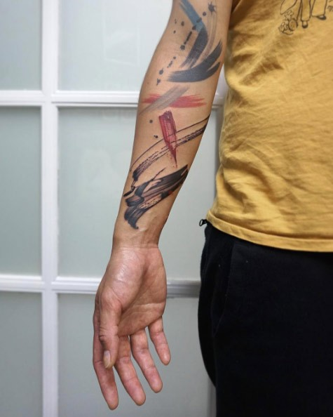 Abstract style colored forearm tattoo of various ornaments