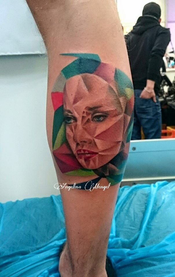 Abstract style colored leg tattoo of unusual looking woman face