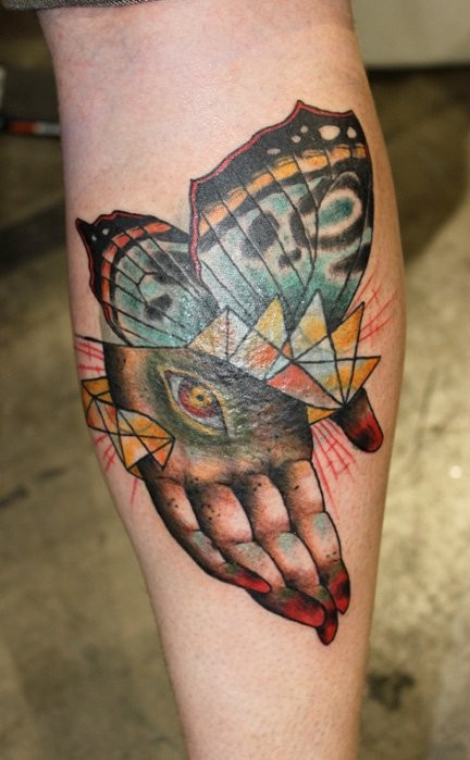 Abstract style colored leg tattoo of human hand with butterfly wings and eye