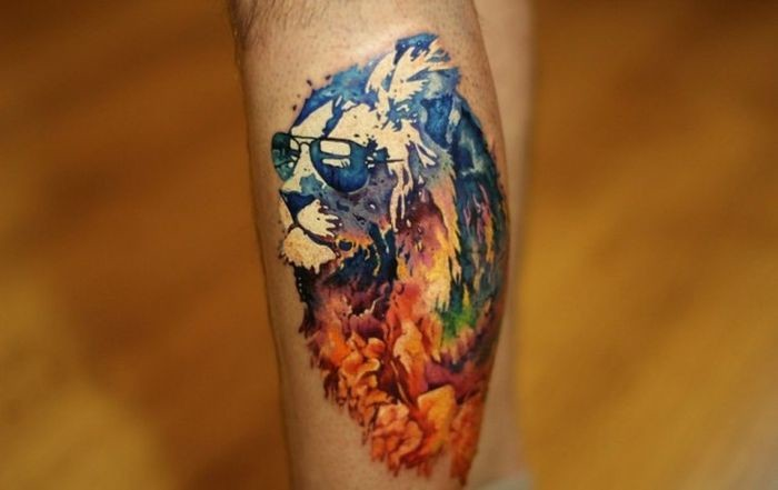 Abstract style colored leg tattoo of lion with sunglasses