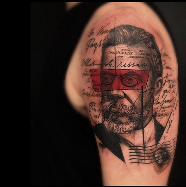 Abstract style colored shoulder tattoo of man portrait with lettering