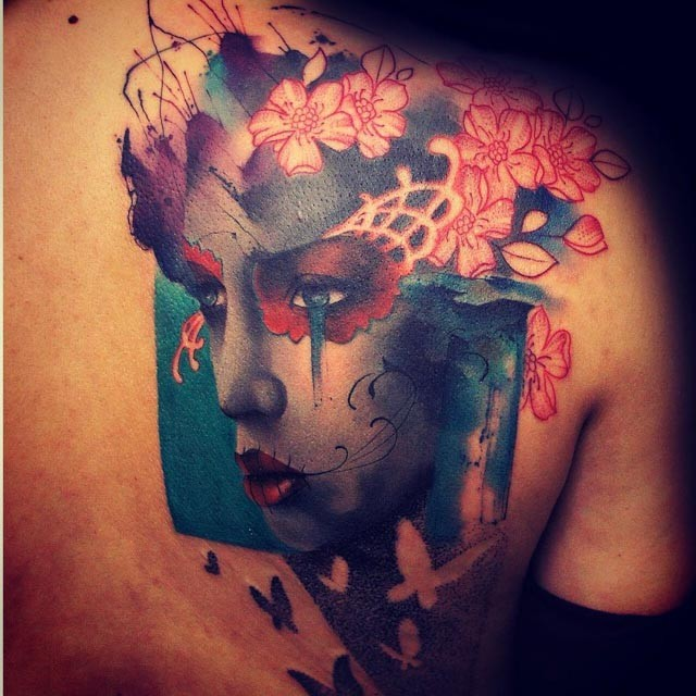 Abstract style colored shoulder tattoo of woman portrait stylized with flowers