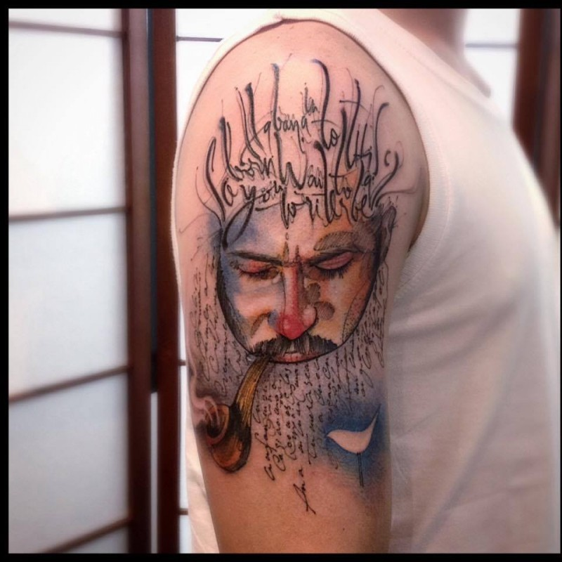 Abstract style colored shoulder tattoo of man with smoking pipe and lettering