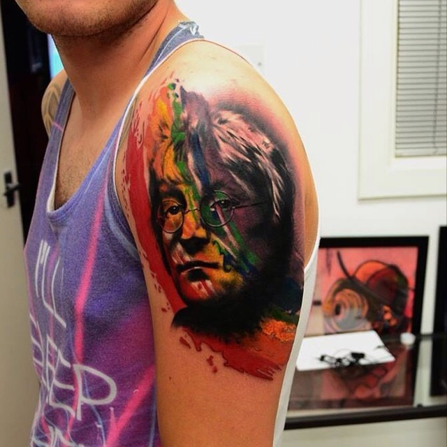 Abstract style colored shoulder tattoo of Lennon face
