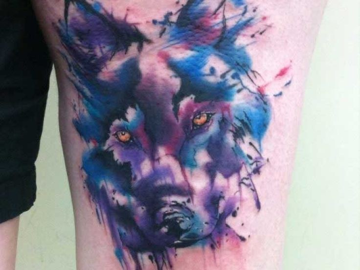 Abstract style colored thigh tattoo of mystical wolf head